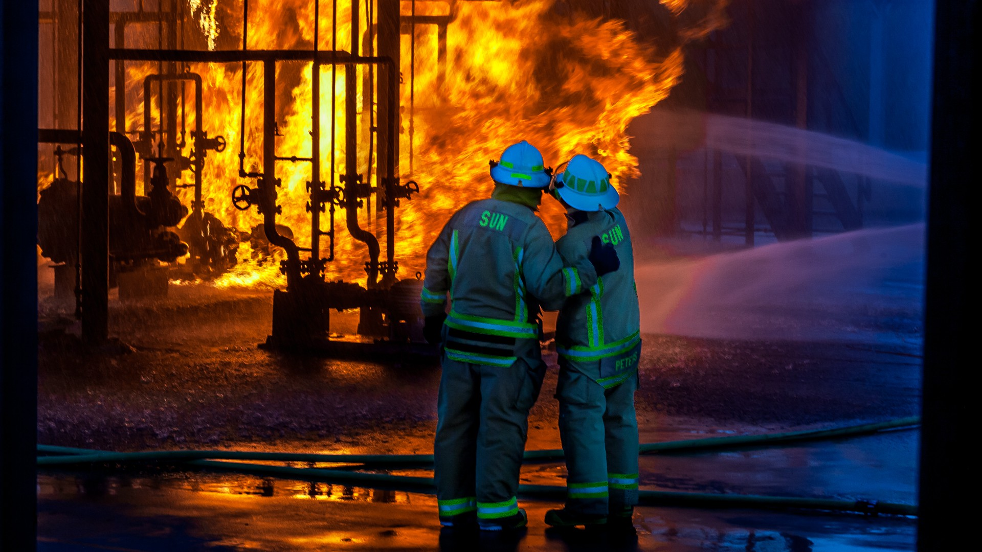 Two fire fighters watching an industrial fire